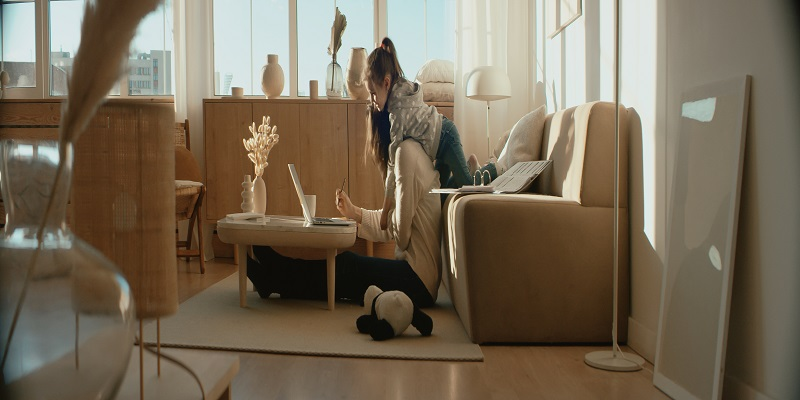Mother working from home, her daughter distracts her and drawing attention