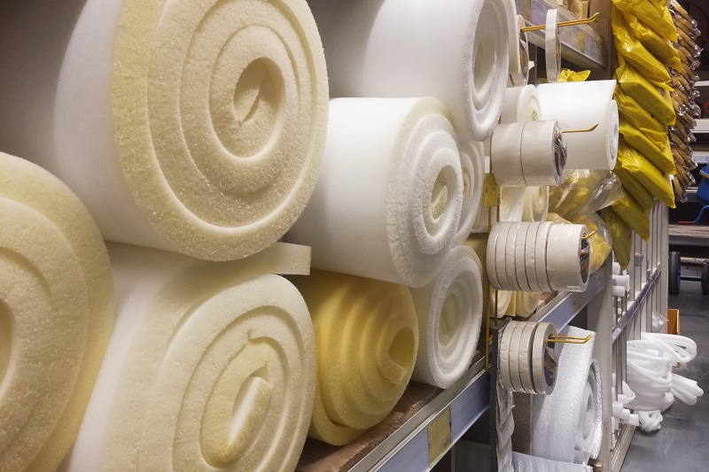 Rolls white and yellow foam rubber building material texture. Polystyrene sealing foam surface background.